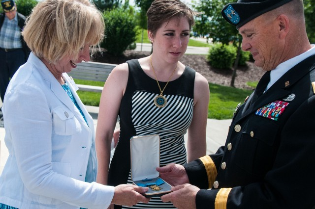 "Maj. Gen. Paul E. Funk II, commanding general, 1st Inf. Div., is handed a Congressional Medal of Honor from Cathy Ehlers Metcalf (left) and Katherine Metcalf (center) after a June 12 ceremony at Victory Park, Fort Riley, Kan. The event honored the division's recent Medal of Honor recipients and Gold Star families by unveiling their memorial stones within the park. Metcalf is the granddaughter of Staff Sgt. Walter D. Ehlers, who received the nation's highest award for valor in 1944 for his actions in Goville, France, passed away Feb. 20. He was the remaining Medal of Honor recipient of the ""Big Red One."" (Sgt. 1st Class Abram Pinnington, 1st Inf. Div.)"