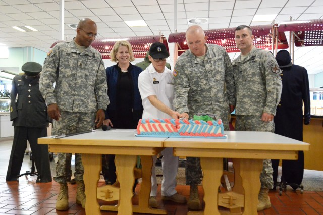 As part of her visit June 12, 2014, Kathleen Y. Marin, Installation Management Command Europe region director, joins selected volunteers to participate in the cake-cutting ceremony inside the Flight Line Inn Dining Facility at Storck Barracks to celebrate the Army's 239th birthday. From left: Command Sgt. Maj. Romeo Montez III, Installation Management Command Europe command sergeant major; Marin; Pfc. Robert Yacotis, food operations specialist at the Flight Line Inn Dining Facility and the youngest Soldier present; Staff Sgt. Dean Spaans, assigned to 3rd Battalion, 58th Aviation Regiment (Airfield Operations), 12th Combat Aviation Brigade, and the oldest Soldier present; and Col. Christopher M. Benson, U.S. Army Garrison Ansbach commander. Montez and Marin, who were visiting from Headquarters, IMCOM Europe, joined Yacotis, Spaans and Benson for an early celebration of the Army's birthday, which is officially June 14. On display behind them are uniforms from time periods throughout Army history.