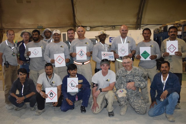 Patrick LeBlanc, 3-401st Army Field Support Battalion-Bagram Airfield safety officer, poses with workers in the Facilities shop who are holding Global Harmonized System of Classification and Labeling of Chemicals pictograms.  (Photo by Summer Barkley, 3-401st AFSBn Public Affairs)