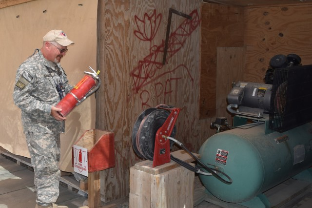 Patrick LeBlanc, 3-401st Army Field Support Battalion-Bagram Airfield safety officer, inspects a fire extinguisher in a work area to ensure it is fully charged and ready for use. (Photo by Summer Barkley, 3-401st AFSBn Public Affairs)