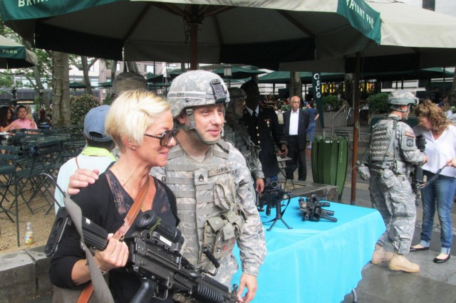 New York Army National Guard Staff Sgt. Daniel Dukin poses with a visitor to the weapons and equipment display the 1st Battalion, 69th Infantry, presented in Bryant Park, New York City, June 13, 2014, as part of events commemorating the 239th Birthday of the United States Army, which is June 14.