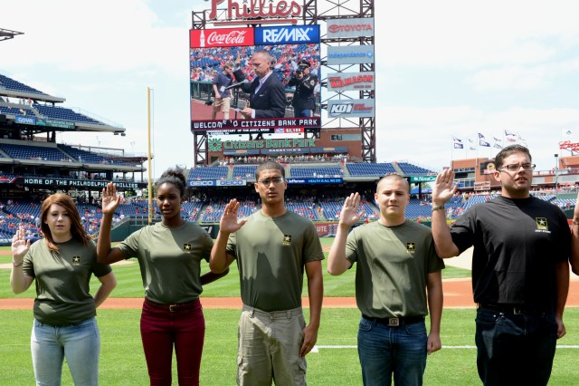 Future Soldiers raise their hands during an enlistment ceremony hosted by Under Secretary of the Army Brad R. Carson, at Phillies Citizens Bank Park Stadium in Philadelphia, June 14, 2014.