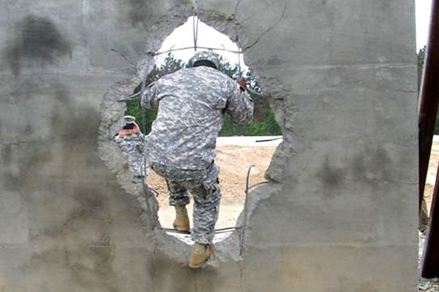 A Soldier steps through a breached, double-reinforced concrete wall at Fort Polk, Louisiana, during a demonstration May 7 of wall-breaching technology.