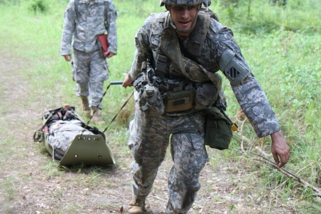 Sgt. Paul Rava, a combat medic with 3rd Battalion, 15th Infantry Regiment, 4th Infantry Brigade Combat Team, 3rd Infantry Division, and a native of Huntington Beach, Calif., pulls a patient to his next objective during Expert Field Medical Badge testing on Fort Stewart, Ga., June 11, 2014. (Photo by Sgt. Joshua Laidacker, 4th IBCT, 3rd ID, Public Affairs)