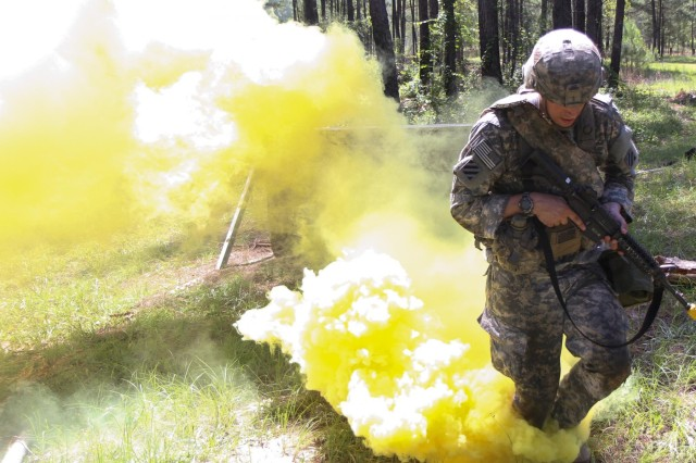 Sgt. Paul Rava, a combat medic with 3rd Battalion, 15th Infantry Regiment, 4th Infantry Brigade Combat Team, 3rd Infantry Division, and a native of Huntington Beach, Calif., runs through smoke he used to conceal his movement over an obstacle during Expert Field Medical Badge testing on Fort Stewart, Ga., June 11, 2014.(Photo by Sgt. Joshua Laidacker, 4th IBCT, 3rd ID, Public Affairs)