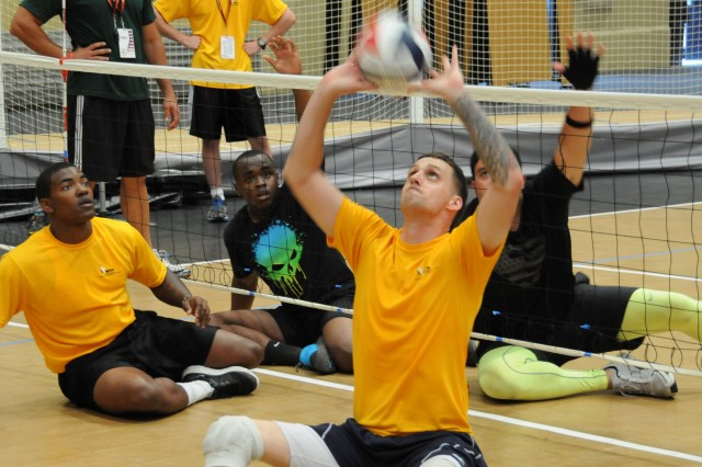 Retired Army Sgt. Matthew Spang, Colorado Springs, Colo., sets a ball during the sitting volleyball competition at the 2014 U.S. Army Warrior Trials, U.S. Military Academy, West Point, N.Y., where more than 100 wounded, ill and injured service members and Veterans from across the United States are competing in archery, basketball, cycling, track and field, swimming, shooting, sitting volleyball and wheelchair basketball.  The Army Green team beat the Marines team in the first round of competition, and will be playing in the championship game against the Air Force team June 18. Army Warrior Trials, June 15-19, are hosted by Warrior Transition Command, and includes athletes with spinal cord injuries, traumatic brain injuries, visual impairment, serious illnesses and amputations. Army Trials help determine athletes who will represent Team Army at the Warrior Games, Sep 28 - Oct 4, Colorado Springs, Colo. (U.S. Army photo by Suzie Ovel)