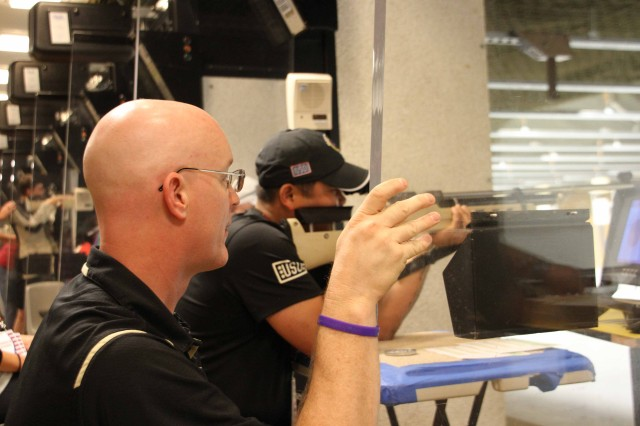 Rick Johnson, U.S. Military Academy assistant rifle coach, offers guidance during shooting competition at U.S. Army Warrior Trials, June 16, 2014.  More than 100 wounded, ill and injured service members and Veterans from across the United States are at the U.S. Military Academy, West Point, N.Y. to train and compete in the Army Warrior Trials, June 15-20.  The event is hosted by Warrior Transition Command and includes athletes from the Army, Marines and Air Force facing off in archery, basketball, cycling, track and field, swimming, shooting, sitting volleyball and wheelchair basketball. Participants in the trials include athletes with spinal cord injuries, traumatic brain injuries, visual impairment, serious illnesses and amputations. (U.S. Army Photo by Michael O'Toole)