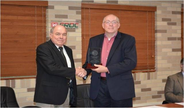 Dr. Holland (ERDC Director) receiving Best AT Program -- CERL