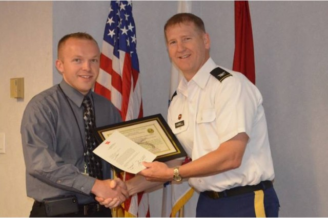 Mr. Robert Bastian receiving AT Honor Roll from COL Ferrell (SPK Cdr).