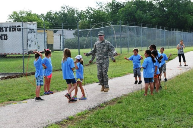 Soldiers with the 166th Aviation Brigade, Division West pose for a photo with the faculty of Gatesville Elementary after the completion of Fun in the Sun Field Day experience in Gatesville, Texas, June 6. (Photo by Nicole Kruse, 166th Aviation Brigade, Division West Public Affairs)