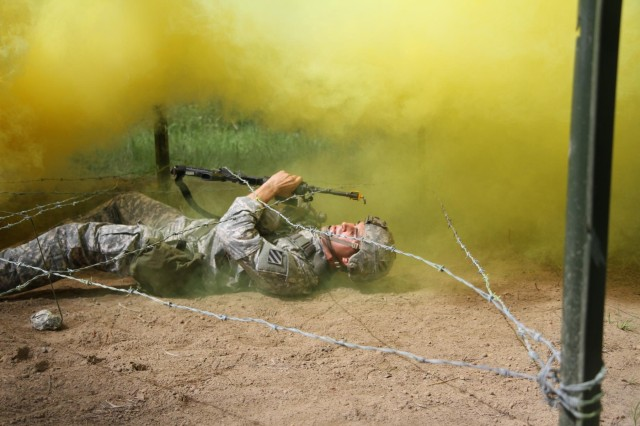 Sgt. Paul Rava, a combat medic with 3rd Battalion, 15th Infantry Regiment, 4th Infantry Brigade Combat Team, 3rd Infantry Division, and native of Huntington Beach, Calif., crawls on his back while utilizing smoke to conceal his movement during Expert Field Medical Badge testing on Fort Stewart, Ga., June 11, 2014. (Photo by Sgt. Joshua Laidacker, 4th IBCT, 3rd ID, Public Affairs)