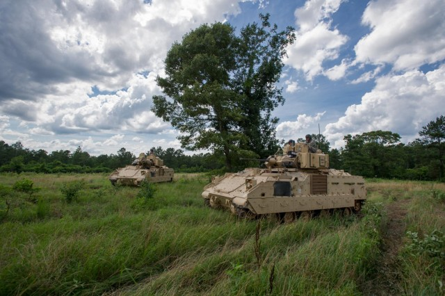 "Soldiers of Company B, 1st Battalion, 64th Armor Regiment ""Desert Rogues,"" 2nd Armored Brigade Combat Team, 3rd Infantry Division, maneuver their M2A3 Bradley Infantry Fighting Vehicles, during an exportable combat training center training event located at Camp Shelby, Miss., June 9, 2014.  At Camp Shelby, the Rogues will act as the opposing force in support of the 278th Armored Cavalry Regiment, a National Guard unit headquartered in Knoxville, Tenn. This event marks the first time a battalion from the Active Component has acted as opposing force for a reserve-component unit since Sept. 11, 2001, due to the active Army's high rate of deployment. Not only does it signify that the Army is getting back to the way it used to be before the conflicts, but it also signifies a large step toward embracing the Total Army Concept. The training exercise is scheduled to be more than a month long, and will be finished in the last week of June."