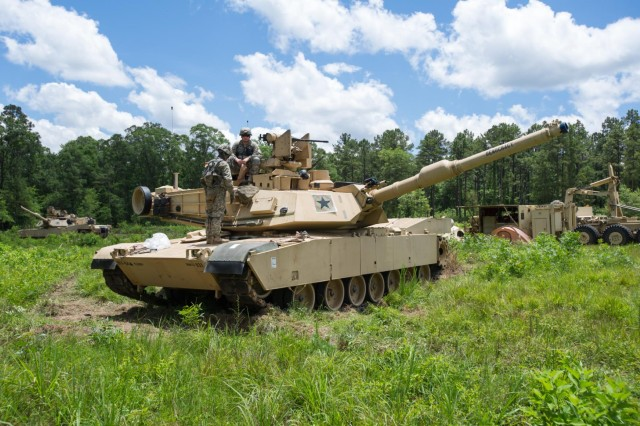 "Soldiers of Company D, 1st Battalion, 64th Armor Regiment ""Desert Rogues,"" 2nd Armored Brigade Combat Team, 3rd Infantry Division, keep an eye out for ""the enemy"" while on their M1A2SEP Abrams Tank, ""Democracy,"" during an exportable combat training center training event located at Camp Shelby, Miss., June 9, 2014. At Camp Shelby, the Rogues will act as the opposing force in support of the 278th Armored Cavalry Regiment, a National Guard unit headquartered in Knoxville, Tenn. This event marks the first time a battalion from the Active Component has acted as opposing force for a reserve-component unit since Sept. 11, 2001, due to the active Army's high rate of deployment. Not only does it signify that the Army is getting back to the way it used to be before the conflicts, but it also signifies a large step toward embracing the Total Army Concept. The training exercise is scheduled to be more than a month long, and will be finished in the last week of June."