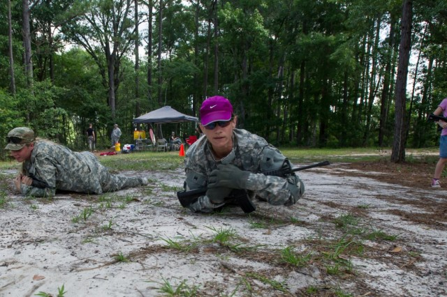"Julie Howell (middle) and Belle Donnelly (left), perform the high-crawl in an obstacle course as part of a Spouse Spur Ride held here by the 3rd Squadron, 7th Cavalry Regiment ""Seventh First,"" 2nd Armored Brigade Combat Team ""Spartans,"" 3rd Infantry Division, May 31. The SSR was an all day event that started with the participating family members having their gear inspected, as well as receiving a safety brief. After that the wives foot marched to the obstacle course, where they ran through many of the obstacles. The event culminated with an award ceremony and a barbecue held at the squadron's motorpool. (U.S. Army Photo by Staff Sgt. Richard Wrigley 2nd ABCT, 3rd ID, Public Affairs NCO)"