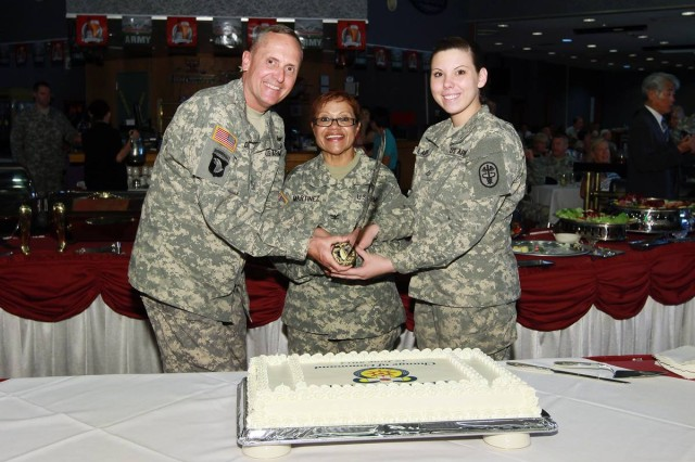 Brig. Gen. Dennis Doyle (left), Commanding General of the Pacific Regional Medical Command and Tripler Army Medical Center, assists Col. Thirsa Martinez (center), newly appointed  Commander of U.S. Army Medical Department Activity Japan in cutting the ceremonial cake during a change of command celebration on June 17, 2014 at Camp Zama, Japan.