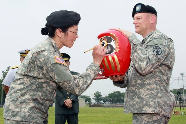 Col. Vivian Hutson (left), U.S. Army Medical Department Activity Japan outgoing Commander, paints a traditional Japanese Daruma Doll, a symbol for luck, during a change of command ceremony where she relinquished command to Col. Thirsa Martinez (not pictured) during an outdoor ceremony at Yano Field, Camp Zama, Japan on June 17, 2014.
