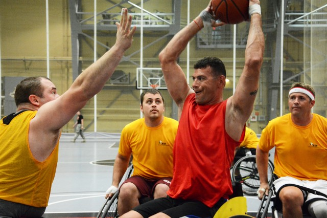 Marine Staff Sgt. Adam Vickery surrounded by a trio of Army yellow during the wheelchair basketball competition