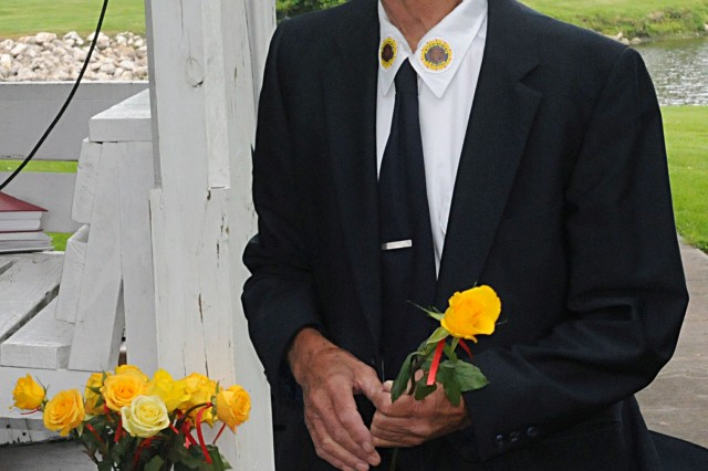 American Legion Post 465 commander, Millard Lindberg, pulls a yellow rose from a bouquet and places it at a memorial stone at Andover Lake Park, Andover, Ill., June 8. (Photo by Sgt. 1st Class Shannon Wright, ASC Public Affairs)