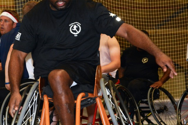 Retired Sgt. 1st Class Charles Armstead, Fort Hood, Texas, directs a teammate during wheelchair basketball play at the 2014 U.S. Army Warrior Trials. Armstead, who began playing wheelchair basketball while assigned to Warrior Transition Brigade, Fort Hood, Texas, now plays for the Harker Heights Hustlers, a local community ball club. More than 100 wounded, ill and injured service members and Veterans from across the United States congregated at West Point to train and compete in the Army Warrior Trials, June 15-19.  The event is hosted by Warrior Command and includes athletes from the Army, Marines and Air Force facing off in archery, basketball, cycling, track and field, swimming, shooting, sitting volleyball and wheelchair basketball. Participants in the trials include athletes with spinal cord injuries, traumatic brain injuries, visual impairment, serious illnesses and amputations.