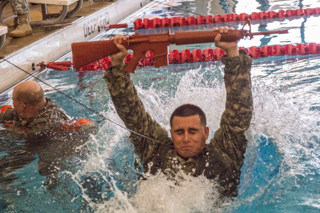 Staff Sgt. Mario A. Saucedo, assigned to Headquarters Company, Network Enterprise Technology Command, jumps into a pool during water survival training during the NETCOM Best Warrior Competition at Fort Huachuca, Ariz., June 9, 2014.