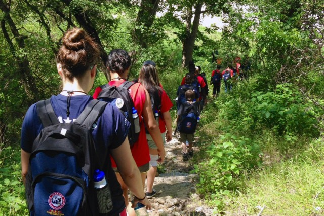 A group of teens hike down a path to a river at the Parrie Haynes Ranch in Killeen, Texas, June 13, 2014, during a TAPS Good Grief Camp Out. TAPS stands for the Tragedy Assistance Program for Survivors.