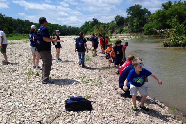 Campers at the four-day, three-night TAPS Good Grief Camp Out toss rocks into a river, symbolizing a feeling they want to let go of, after a hike to the water at Parrie Haynes Ranch in Killeen, Texas, June 13, 2014. TAPS stands for the Tragedy Assistance Program for Survivors.