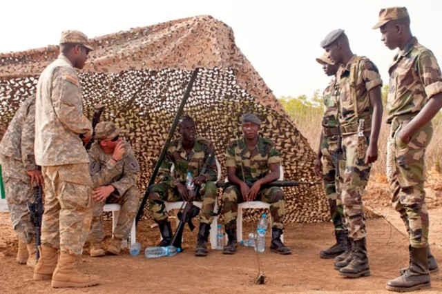 Staff Sgt. Justin Vance, Pfc. Raul Yang and Pfc. Desi Montgomery, infantry Soldiers with 1st Battalion, 28th Infantry Regiment, 1st Infantry Division, talk with Senegalese Soldiers while on guard at the Ammunition Holding Area. The Soldiers are participating in Exercise Western Accord 14 in Senegal, Africa. Exercise Western Accord is a partnership exercise between the United States, Senegal, France, Netherlands and other partner nations, which is designed to increase interoperability between military forces and ensure the common ability to conduct peace operations throughout western Africa.