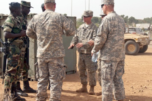 Soldiers with 1st Battalion, 28th Infantry Regiment, 1st Infantry Division talk with Senegalese Soldiers before the start of Exercise Western Accord 14. The Soldiers are participating in Exercise Western Accord, a partnership exercise between the United States, Senegal, France, Netherlands and other partner nations, which is designed to increase interoperability between military forces, and ensure the common ability to conduct peace operations throughout western Africa.