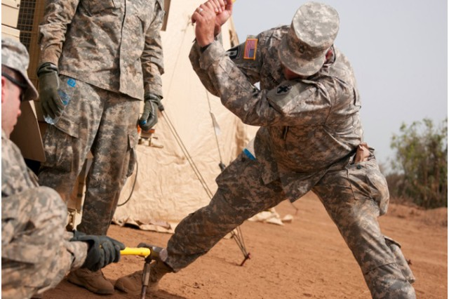 Sgt. 1st. Class Frank Rivera, a combat medic, hammers a grounding rod into the ground and gives a break to Spc. Luis Grajales, generator equipment repairer and Spc. Jose Martinez, a medical laboratory. All three Soldiers are with 335th Area Support Medical Company and are participating in Exercise Western Accord 14. Exercise Western Accord is a partnership exercise between the United States, Senegal, France, Netherlands and other partner nations, which is designed to increase interoperability between military forces, and ensure the common ability to conduct peace operations throughout western Africa.
