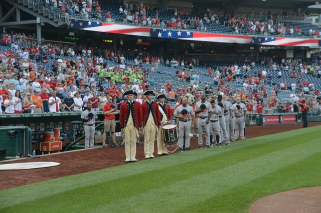 The U.S. Army Old Guard Fife and Drum Corps stand on the field during the national anthem as part of the Washington Nationals Army Day celebration, June 18, 2014.