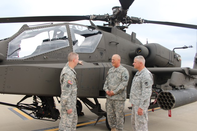 The Aviation and Missile Command's Maj. Gen. Jim Richardson, center, talks about the new capabilities of the latest Apache helicopter model with Chief Warrant Officer 4 Michael Kennedy, left, and AMCOM Command Sgt. Maj. Tod Glidewell. Richardson, an Apache pilot, got a close look at the new Apache during a tour of the Redstone Test Center's Aviation Test Flight Directorate at the Redstone Airfield. Kennedy is an Apache experimental test pilot. Richardson assumed command of AMCOM on June 12.