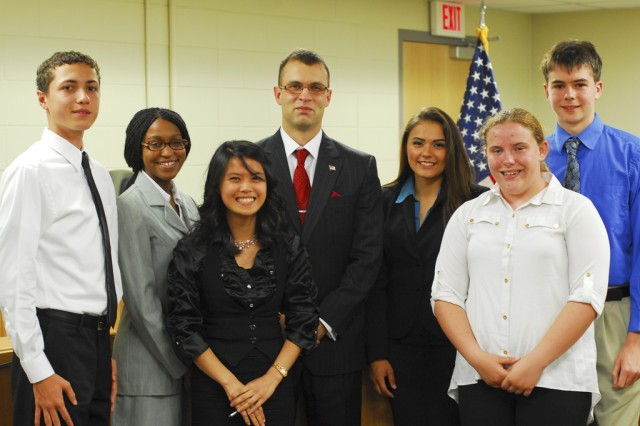 From left, Andrew Von Weber (2nd chair prosecutor), Cjeylon Curry (1st chair prosecutor), Kate Caberte (1st chair defense), Capt. Trent Kubasiak (mock trial coach), 2nd Lt. Ashley White (mock trial coach), Kathleen Crosby (2nd chair defense) and Steven Isaacs (defendant) were the lead participants in the mock legal trial exercise, held June 7, in the courtroom at the Humphreys Consolidated Legal Center. Kubasiak developed the program. -- U.S. Army photo by Effy An and Helena Kim