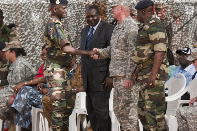 Col. Elhadji Babacar Faye, Deputy Chief of Army Staff shakes hands with Brig. Gen. Kenneth Moore, United States Army Africa Deputy Commander following Faye's speech during the opening day ceremony of Exercise Western Accord, June 16. Exercise Western Accord is a U.S. Africa Command sponsored, and USARAF-hosted annual joint training partnership exercise between the United States, the Economic Community of West African States and partner nations. The exercise, held in Senegal this year, is designed to increase interoperability between military forces and ensure the common ability to conduct peace operations throughout western Africa.