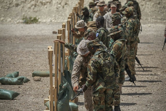 Marines with the 3rd Bn., 23rd Marine Regiment assist Ghanaian Soldiers in battle sight zeroing their weapons during a firing range June 19. The firing range was a part of Exercise Western Accord, a U.S. Africa Command sponsored  and U.S. Army Africa led annual joint training partnership exercise between the United States, the Economic Community of West African States and partner nations. The exercise, held in Senegal this year, is designed to increase interoperability between military forces and ensure the common ability to conduct peace operations throughout western Africa.