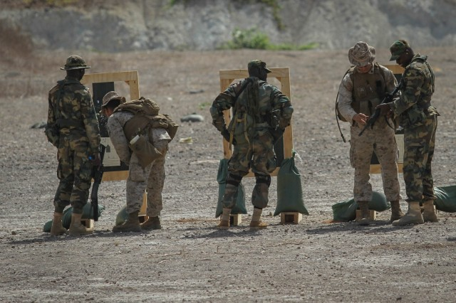 Cpl. Santos Berumen (left), team leader and position safety officer and Sgt. Chase Ogden, squad leader and position safety officer, both with the 3rd Bn., 23rd Marine Regiment, assist Ghanaian Soldiers in battle sight zeroing their weapons during a firing range June 19. The firing range was a part of Exercise Western accord, a U.S. Africa Command sponsored and U.S. Army Africa ledannual joint training partnership exercise between the United States, the Economic Community of West African States and partner nations. The exercise, held in Senegal this year, is designed to increase interoperability between military forces and ensure the common ability to conduct peace operations throughout western Africa.