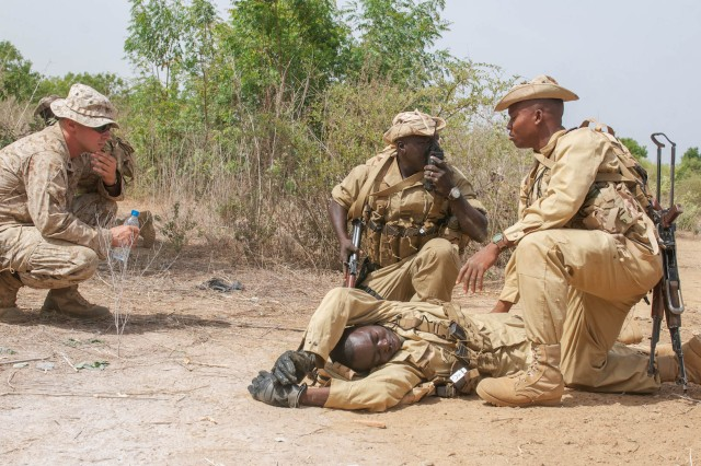 Marine Sgt. Bryan Ballard, an infantryman and class instructor with India Co., 3rd Bn., 23rd Marine Regiment, observes Burkina Faso Soldiers as they simulate treating a casualty during the Improvised Explosive Device detection class June 20. The unit trained Soldiers from different nations in various techniques and procedures for detecting and reacting to IEDs during Exercise Western Accord. Exercise Western Accord is a U.S. Africa Command sponsored and U.S. Army Africa led annual joint training partnership exercise between the United States, the Economic Community of West African States and partner nations. The exercise, held in Senegal this year, is designed to increase interoperability between military forces and ensure the common ability to conduct peace operations throughout western Africa.
