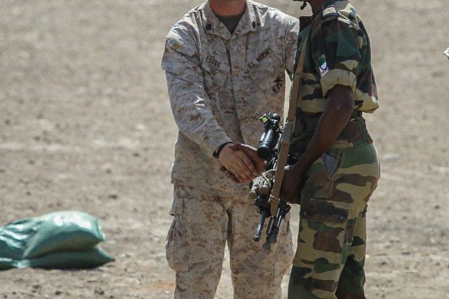 Staff Sgt. Daniel Estes, range noncommissioned officer in charge, 3rd Bn., 23rd Marine Regiment, congratulates a Ghanaian Soldier for successfully zeroing his weapon during a firing range June 19. The firing range was a part of Exercise Western Accord, a U.S. Africa Command sponsored and U.S. Army Africa ledannual joint training partnership exercise between the United States, the Economic Community of West African States and partner nations. The exercise, held in Senegal this year, is designed to increase interoperability between military forces and ensure the common ability to conduct peace operations throughout western Africa.