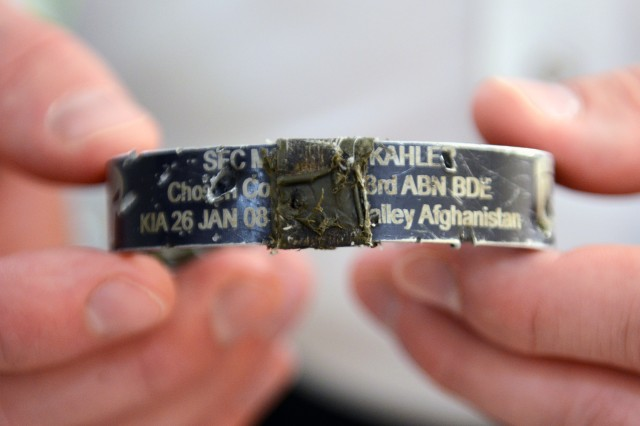 In his New Hampshire home, May 3, 2014, Ryan Pitts holds the KIA bracelet he was wearing the time of the attack in Wanat, Afghanistan. The bracelet honors Sgt. 1st Class Matthew Kahler, platoon sergeant of 2nd platoon who was died Jan. 26, 2008, after being shot by an Afghan guard in Waygul, Afghanistan. The bracelet is taped over another bracelet (not visible) the commemorates the fallen of 1st Platoon, Chosen Company, who were killed Nov. 9, 2007, in an ambush. Commemorated on the second bracelet are: Capt. Matthew Ferrara, Spc. Joseph Lancour, Cpl. Lester Roque, Cpl. Sean Langevin and Sgt. Jeffrey Mersman. This bracelet prevented shrapnel from penetrating Pitts' wrist.
