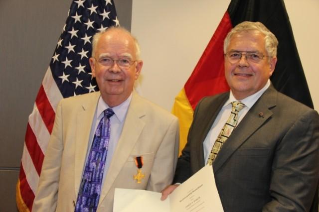 Edgewood Chemical Biological Center's Dr. Jim Baker (left) receives the German Gold Cross of Honour from Dr. Alexander Grabowski (right).