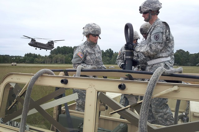 Soldiers from the 53rd Movement Control Battalion, 7th Sustainment Brigade, prepare a humvee for hook up to a Chinook helicopter during sling-load training at Felker Army Airfield.
