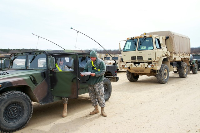 A movement control specialist assigned to the 329th Movement Control Team, discusses a convoy clearance with a Soldier during Warrior Exercise 86-14-02.
