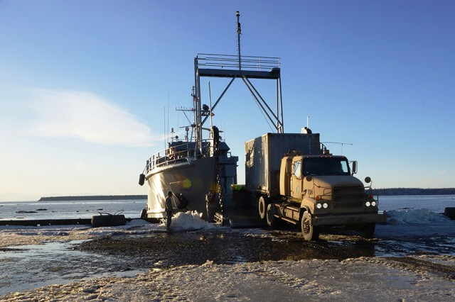 A landing craft utility establishes a waterborne main supply route at a degraded port, simulating the delivery of vehicles and humanitarian aid to those affected by an earthquake and tsunami during JLOTS 2014. (Photo by Maj. Mike Harris)