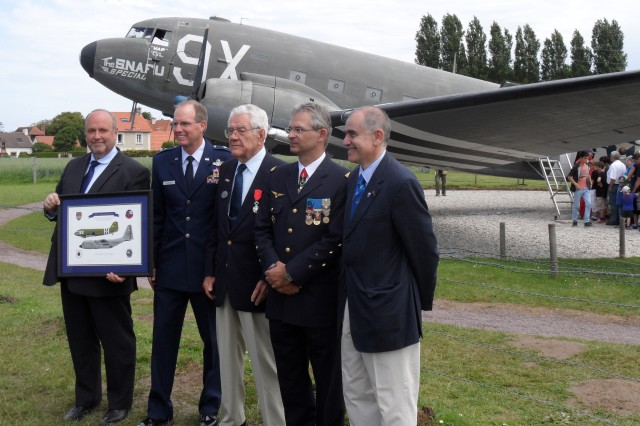 Gene Noble, center, receives the French Legion of Honour medal at a ceremony June 7 in Merville-Franceville, France, in front of the C-47 he had a role in restoring for the town's World War II air memorial. Also pictured are French and American dignitaries, including Brig. Gen. James Scanlan (second from left), commander of the 440th Airlift Wing at Pope Field, North Carolina. The unit traces its heritage to the 440th Troop Carrier Group, in which Noble served as a pilot on D-Day.