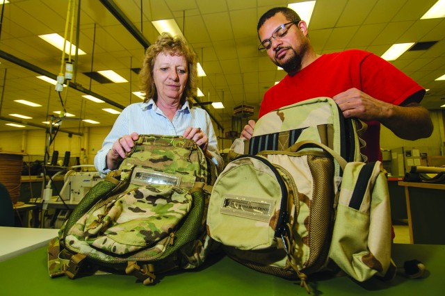 Fabric Workers Phyllis Miller and David Smith inspect two backpack prototypes designed to support the tactical radio mission. The packs were also fabricated here. The technicians and other members of Tobyhanna's Equipage Branch manufacture, repair and modify tarpaulins, carrying cases, protective covers and support equipment for Command, Control, Communications, Computers, Intelligence Surveillance and Reconnaissance (C4ISR) equipment using hot air welding and industrial sewing. Their duties include recovering, relining and replacing hardware, fittings, trimmings and rubber on a variety of items. Employees also fabricate custom stamps using a computerized photopolymer process, plus install insulating material, floors, and electro-magnetic interference, radio frequency interference and environmental seals and gaskets in C4ISR equipment. The branch is part of the depot's Systems Integration and Support Directorate.
