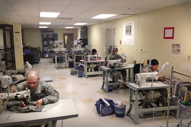 Soldiers work at their sewing machines at the Joint Base Lewis-McChord, Wash., Post Fabric Renovation and Sewing Shop.
