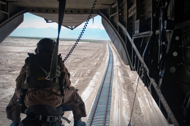 The rear gunner in a Sikorsky UH-53 helicopter watches the end of the Hairatan-Uzbekistan railroad stretch into the distance. The 47-mile line provides a valuable commercial link between Afghanistan and Uzbekistan, across the Amu Darya River.