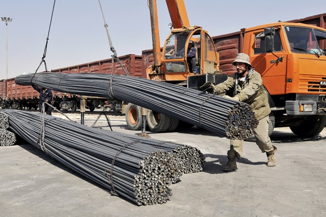 Steel rebar, imported through Uzbekistan, is guided into place after a crane lifts the rods out of a railroad gondola car at Rail Port 4, in Niababad, Afghanistan. After offloading the rebar from the railcar and staging on the loading dock, the rebar is then lifted onto trucks for transportation to construction sites around Afghanistan.