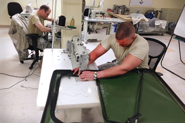 A Soldier repairs tears on a humvee door using a long-arm sewing machine.