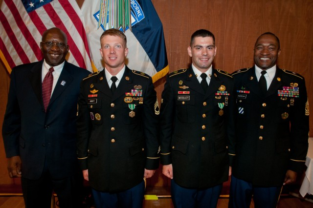 Sgt. 1st Class Cameron Abbott (center left) and Spc. Michael McCollett (center right), both representing 16th Military Police Brigade, are recognized by retired Cmd. Sgt. Maj. Andrew McFowler (left) and Cmd. Sgt. Maj. Jesse Andrews (right) are recognized as the XVIII Airborne Corps Noncommissioned Officer and Soldier of the Year 2014, at McKellar's Lodge, June 20. Selected from field of 20 top competitors from across the XVIII Abn. Corps, Abbott and McCollett will now go on to compete at the Army Forces Command level completion later this summer.