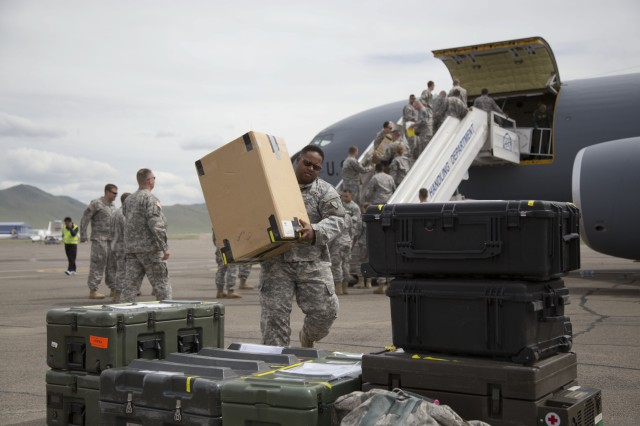Alaska Army National Guardsmen Capt. Gregory Vanison, Joint Forces Headquarters, carries medical supplies off a 168th Air Refueling Wing KC-135, after arriving in Ulaanbaatar, Mongolia, June 16, 2014.